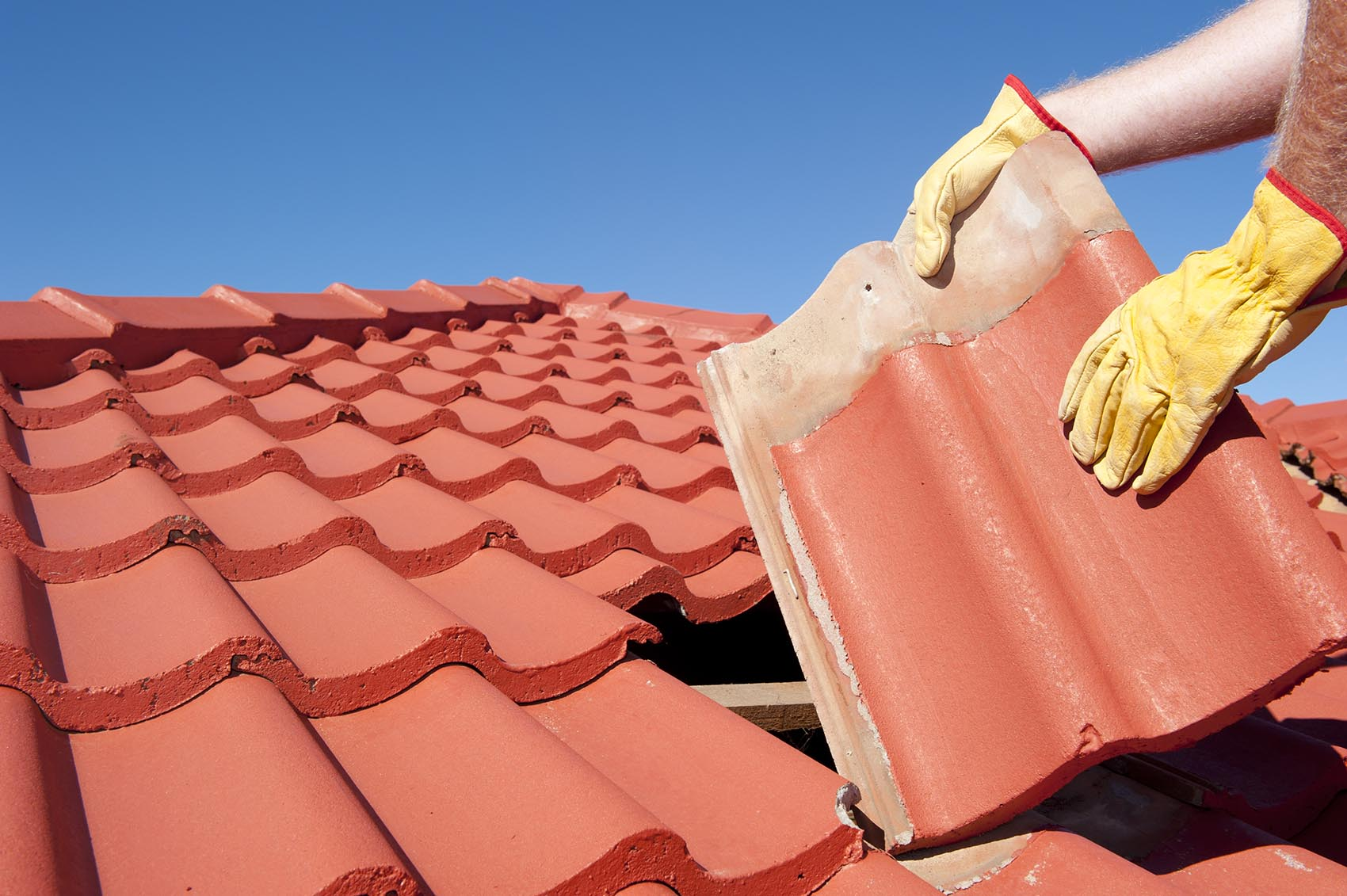worker tile roofing repair house